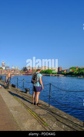 Shadwell Basin, London, UK - May 7, 2018: Portrait view of Shadwell Basin with a man in the foreground and someone fishing.  Taken in May on a bright  - Stock Photo