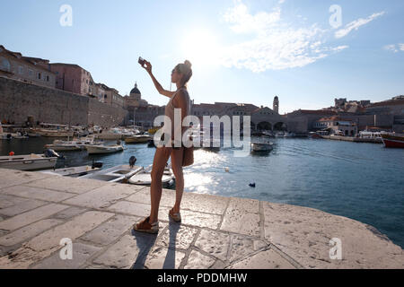 Tourist taking a selfie with her smartphone at the harbor in Dubrovnik, Croatia, Europe - Stock Photo