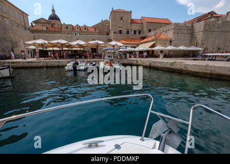 Boat arriving at the harbor in Dubrovnik old town, Croatia, Europe - Stock Photo
