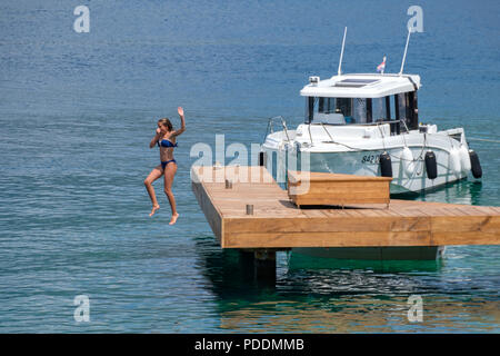 Teenage girl jumping off a dock into the water - Stock Photo