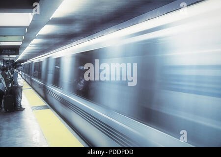 Waiting for the subway in downtwon San Francisco, California, USA. The original photo has been digitally altered to give it a bluish, dreamlike efect. - Stock Photo