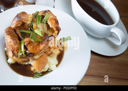 An English pub/restaurant dish of individual Toad in the Hole on a bed of mashed potato served with rich brown gravy sauce. - Stock Photo