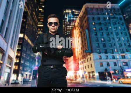 Police officer in sunglasses, night city - Stock Photo