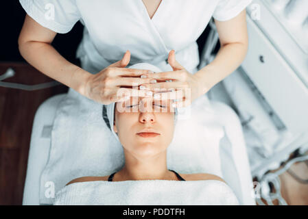 Beautician rubs the cream on female patient face - Stock Photo