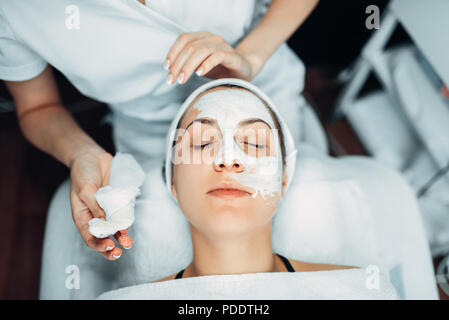 Beautician hands with cream against patient face - Stock Photo