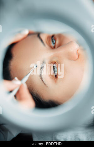 Patient face, view on through a magnifying glass - Stock Photo