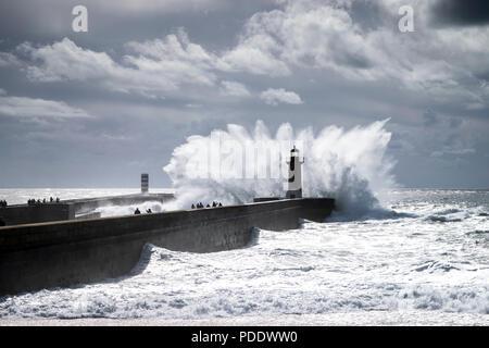 Waves crashing over a lighthouse in Foz do Douro, Porto , Portugal - Stock Photo
