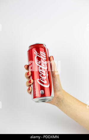 Atlanta, Georgia, USA - July 22, 2018: woman hand with red nails holding aluminum can coca-cola classic from with white painted logo from USA on white background - Stock Photo