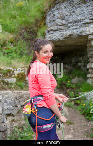 Photo of smiling female climber standing next to mountain against background of green landscape - Stock Photo
