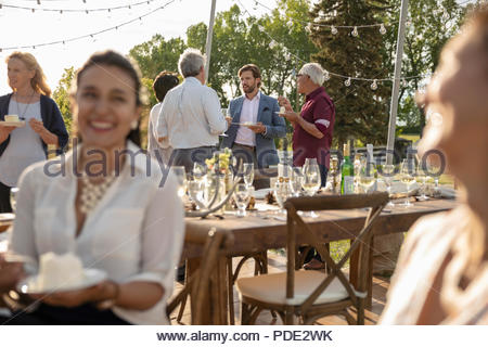 Friends eating cake and talking, celebrating at sunny garden party - Stock Photo
