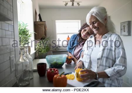 Affectionate daughter and senior mother cooking, cutting vegetables in kitchen - Stock Photo
