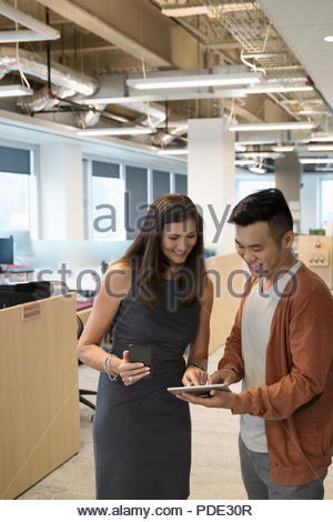 Businessman and businesswoman using digital tablet and smart phone in office corridor - Stock Photo