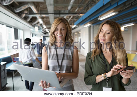 Businesswomen walking with laptop and smart phone in office - Stock Photo