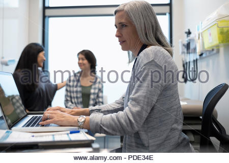 Female doctor typing at laptop in exam room with patient and mother in background - Stock Photo
