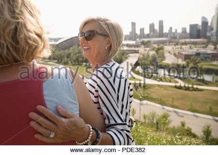 Affectionate mother and daughter walking in urban park - Stock Photo