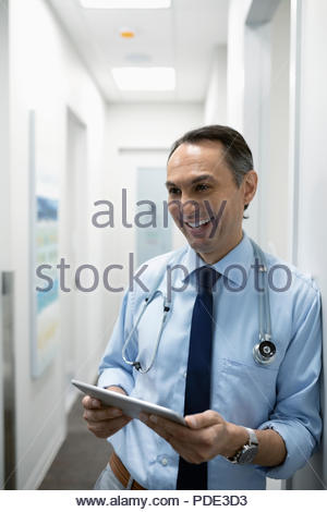 Smiling male doctor using digital tablet in clinic corridor - Stock Photo