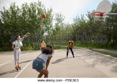 Teenage girl friends playing basketball at park basketball court - Stock Photo
