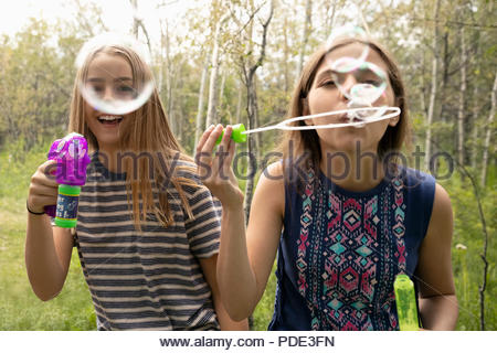 Portrait playful tween girl friends playing with bubble wands - Stock Photo
