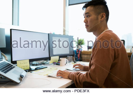 Focused businessman using laptop and computers at desk in office - Stock Photo