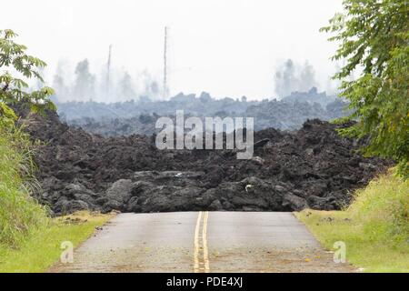 A lava roadblock covers a residential road May 12, 2018, at Leilani Estates, Pahoa, Hawaii. Members of the Hawaii Army and Air National Guard have been activated in order to assemble Task Force Hawaii, which is providing traffic assistance, presence patrols and supporting local government agencies with the volcano outbreak relief effort. - Stock Photo