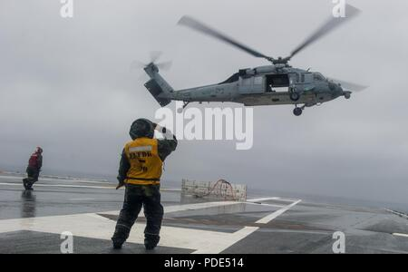 WATERS SOUTH OF JAPAN (May 14, 2018) Aviation Boatswain's Mate (Handling) 1st Class Thinh Dai salutes an MH-60S Sea Hawk, assigned to the Military Sealift Command (MSC) dry cargo/ammunition ship USNS Cesar Chavez (T-AKE 14), after delivering ordnance on the flight deck aboard the Navy's forward-deployed aircraft carrier, USS Ronald Reagan (CVN 76), as part of a replenishment-at-sea during sea trials. The non-combatant, civilian-crewed ship, operated by MSC, provides fuel, food, ordnance, spare parts, mail and other supplies to Navy ships throughout the world. Ronald Reagan, the flagship of Car - Stock Photo