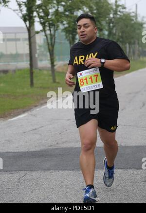 U.S. Army Chief Warrant Officer 2 William Uhila, native to Freemont, California assigned to the 65th Medical Brigade, conducts a two mile run at the Army Physical Fitness Test during the Eighth Army 2018 Best Warrior Competition, held at Camp Casey, Republic of Korea, May 14, 2018.  The Eighth Army Best warrior Competition is being held to recognize and select the most qualified junior enlisted and non-commissioned officer to represent Eighth Army at the U.S. Army Pacific Best Warrior Competition at Schofield Barracks, HI. The competition will also recognize the top performing officer, warrant - Stock Photo
