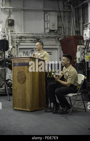 OCEAN (May 15, 2018) Ship's Serviceman 1st Class Michael Burdios, from Long Beach, California, and Electronics Technician 3rd Class Roland Enriquez, from Harmon, Guam, sing at an Asian American Pacific Islander Heritage Month celebration in the hangar bay aboard USS John C. Stennis (CVN) 74. John C. Stennis is underway conducting routine training as it continues preparing for its next scheduled deployment. - Stock Photo