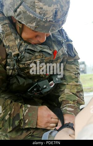 Chief Warrant Officer 2 William Uhila applies a tourniquet to a simulated casualty during the day stakes portion of the Eighth Army 2018 Best Warrior Competition, held at Camp Casey, Republic of Korea, May 17. The Eighth Army Best Warrior Competition is being held to recognize and select the most qualified junior enlisted and non-commissioned officer to represent Eighth Army at the U.S. Army Pacific Best Warrior Competition at Schofield Barracks, HI. The competition will also recognize the top performing officer, warrant officer and Korean Augmentation to the U.S. Army soldier at the Eighth Ar - Stock Photo