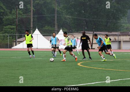 CAMP CASEY, Republic of Korea – KATUSA Pfc. SuChun Hwang, a native of Seoul, and medic assigned to Headquarters and Headquarters Battalion, 2nd Infantry Division/ROK-U.S. Combined Division plays soccer with his team during the 2018 during the 2018 Korean Augmentation to the United States Army (KATUSA)/U.S. Soldier Friendship Week (KUSFW) at Camp Casey, May 17. KUSFW brought KATUSAs and U.S. Soldiers within the 2nd Infantry Division/ROK-U.S. Combined Division together for a week of traditional American and Korean sports competitions to strengthen the alliance and teamwork between U.S. Soldiers  - Stock Photo