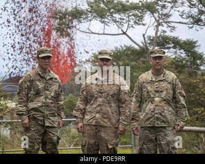 Col. Neal Mitsuyoshi, Brig. Gen. Kenneth Hara and Col. David Williamson, the Hawaii National Guard Joint Task Force 5-0 command team, stand in front of an erupting lava fissure May 18, 2018, at Leilani Estates, Pahoa, Hawaii. Joint Task Force 5-0 has been assembled and called upon by Hawaii Governor David Ige, in order to aid victims of an ongoing volcano outbreak through the use of national guard and active duty resources. - Stock Photo