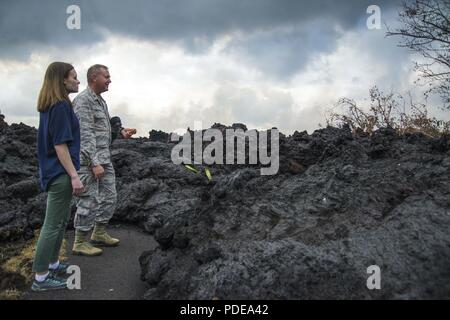 Pāhoa, Hawaii, May 18, 2018 – FEMA employee Meghan Breitenbach and U.S. Air Force Lieutenant Colonel Chuck Anthony view a portion of the hardened lava flow from the Kīlauea volcanic eruption. At the request of the state, FEMA staff are on the ground to support local officials with life-saving emergency protective measures, debris removal, and the repair, replacement, or restoration of disaster-damaged publicly-owned facilities. - Stock Photo
