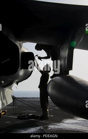 U.S. 5TH FLEET AREA OF OPERATIONS (May 20, 2018) Marine Corps Sgt. Amanda Gomez (bottom), from Chicago, and Lance Cpl. Bryan Pozo, from Kannapolis, N.C., extract a barrel nut from AV-8B Harrier jet, attached to Marine Medium Tiltrotor Squadron 162 (Reinforced), on the flight of the Wasp-class amphibious assault ship USS Iwo Jima (LHD 7), May 20, 2018. Iwo Jima, homeported in Mayport, Fla., is deployed to the U.S. 5th Fleet area of operations in support of maritime security operations to reassure allies and partners, and preserve the freedom of navigation and the free flow of commerce in the re - Stock Photo
