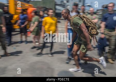 MEDITERRANEAN SEA (May 20, 2018) - U.S. Marine Corps Sgt. Demarcus Roberts, an assault amphibious vehicle commander, assigned to Fox Company, Battalion Landing Team, 2nd Battalion, 6th Marine Regiment, 26th Marine Expeditionary Unit (MEU) sprints across the flight deck during a Steel Beach event aboard the Harpers Ferry-class dock landing ship USS Oak Hill (LSD 51) while underway in the Mediterranean Sea, May 20, 2018. Oak Hill, home ported in Virginia Beach, Virginia, and the 26th MEU are conducting naval operations in the 6th Fleet area of operations. - Stock Photo