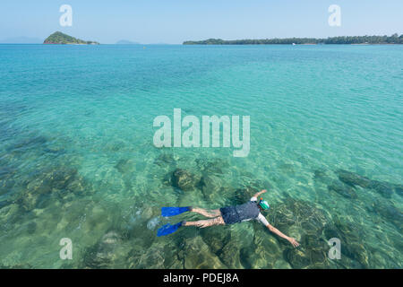 Tourists snorkel in crystal turquoise water near tropical resort in Phuket, Thailand. Summer, Vacation, Travel and Holiday concept. - Stock Photo