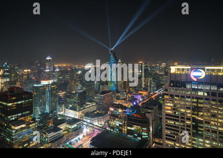 Night view with skyscraper in business district in Bangkok Thailand. Light show at Magnolias Ratchaprasong in Bangkok, Thailand. - Stock Photo