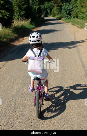 Young girl riding a bicycle along a country lane - Stock Photo