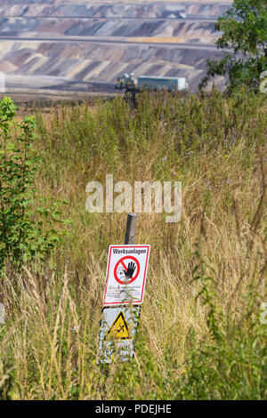 warning sign at the Garzweiler brown coal mine in Germany - Stock Photo