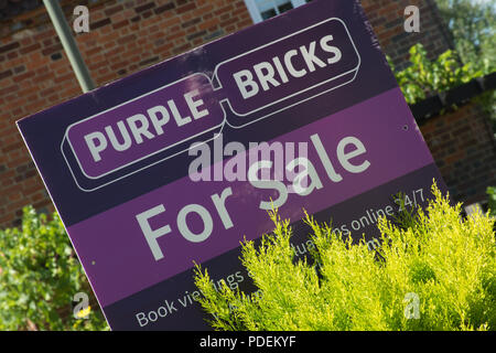 Purple bricks estate agent's for sale sign outside a house in Surrey, UK - Stock Photo