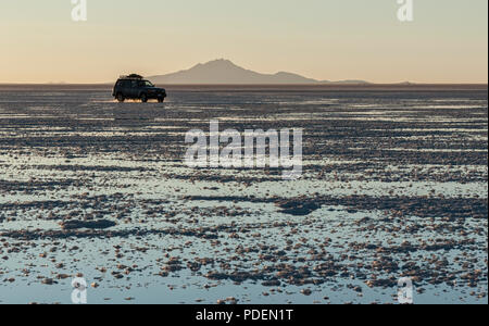 Off-road car in the Salar de Uyuni during sunset. It is the largest salt flat in the World UNESCO World Heritage Site - Altiplano, Bolivia - Stock Photo