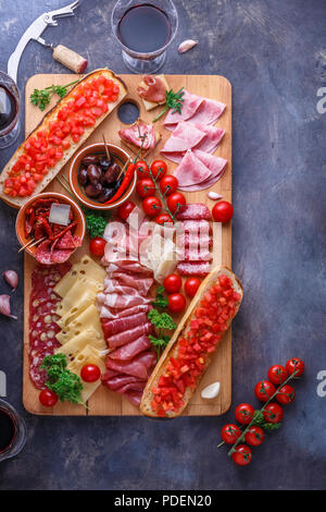 Salami, sliced ham, sausage, prosciutto, cheese, tomato. Meat antipasto board on stone table. Top view with copy space. - Stock Photo