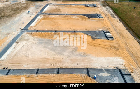 Aerial view from the construction site for a new development with four asphalted dead ends and the sand planum in between. - Stock Photo