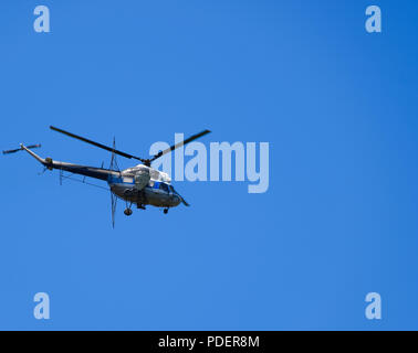A helicopter of agricultural aviation is flying in the blue sky. - Stock Photo