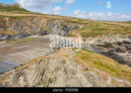 Rugged rocky bay next to Whitesands Beach in Pembrokeshire South Wales on a sunny clear day with white puffy clouds - Stock Photo