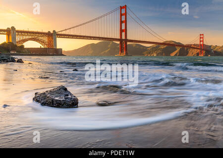 Long exposure of a stunning sunset at the beach by the famous Golden Gate Bridge in San Francisco, California - Stock Photo