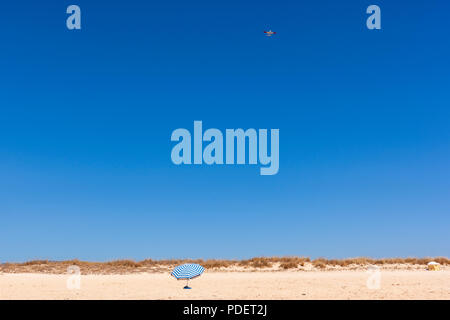 Parasol and a Piper PA-28-161 Warrior II flying over Praia do Alvor, Alvor, Algarve, Portugal - Stock Photo
