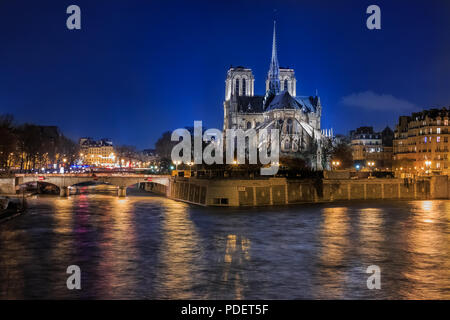 View over the river Seine onto illuminatred back side of Notre Dame de Paris Cathedral at night in, the world famous Gothic Roman Catholic cathedral i - Stock Photo