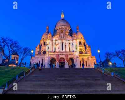Illuminated Basilica of Sacre Coeur in Montmartre in Paris, France at sunset - Stock Photo