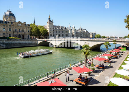 The banks of the Seine during Paris-Plages summer event with a tour boat passing under the Pont au Change and the Palais de la Cite in the background. - Stock Photo