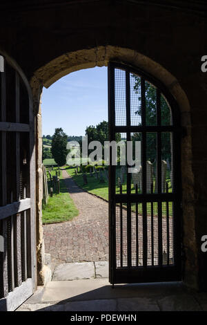 A view through an open church door to the countryside beyond; the church of St Michael, Coxwold, North Yorkshire - Stock Photo