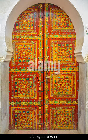 Old wooden intricately carved, studded door and door-frame,of a traditional Moroccan house in Fes, Morocco - Stock Photo